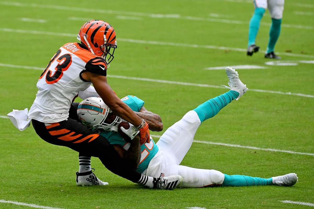 Xavien Howard holds on to an interception on the ground as Bengals receiver Tyler Boyd pulls at the ball during a game in 2020