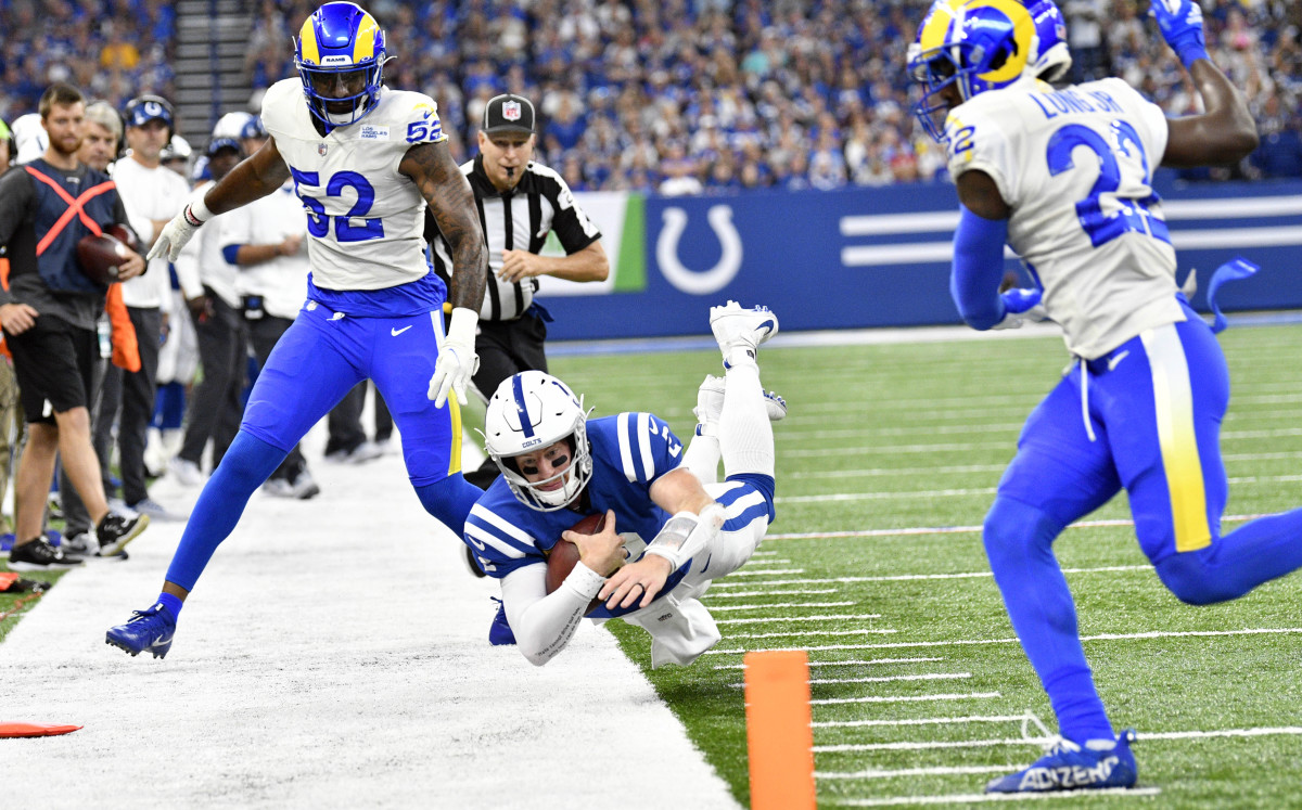 Sep 19, 2021; Indianapolis, Indiana, USA; Indianapolis Colts quarterback Carson Wentz (2) dives out of bounds in front of Los Angeles Rams wide receiver Robert Woods (2) and Los Angeles Rams defensive back David Long (22) during the second half at Lucas Oil Stadium. Rams win 24-21. Mandatory Credit: Marc Lebryk-USA TODAY Sports