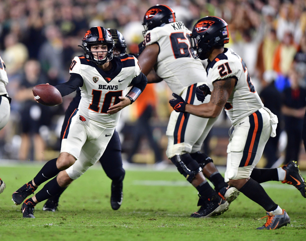 Oregon State quarterback Chance Nolan (10) hands the ball off to running back Trey Lowe (21).