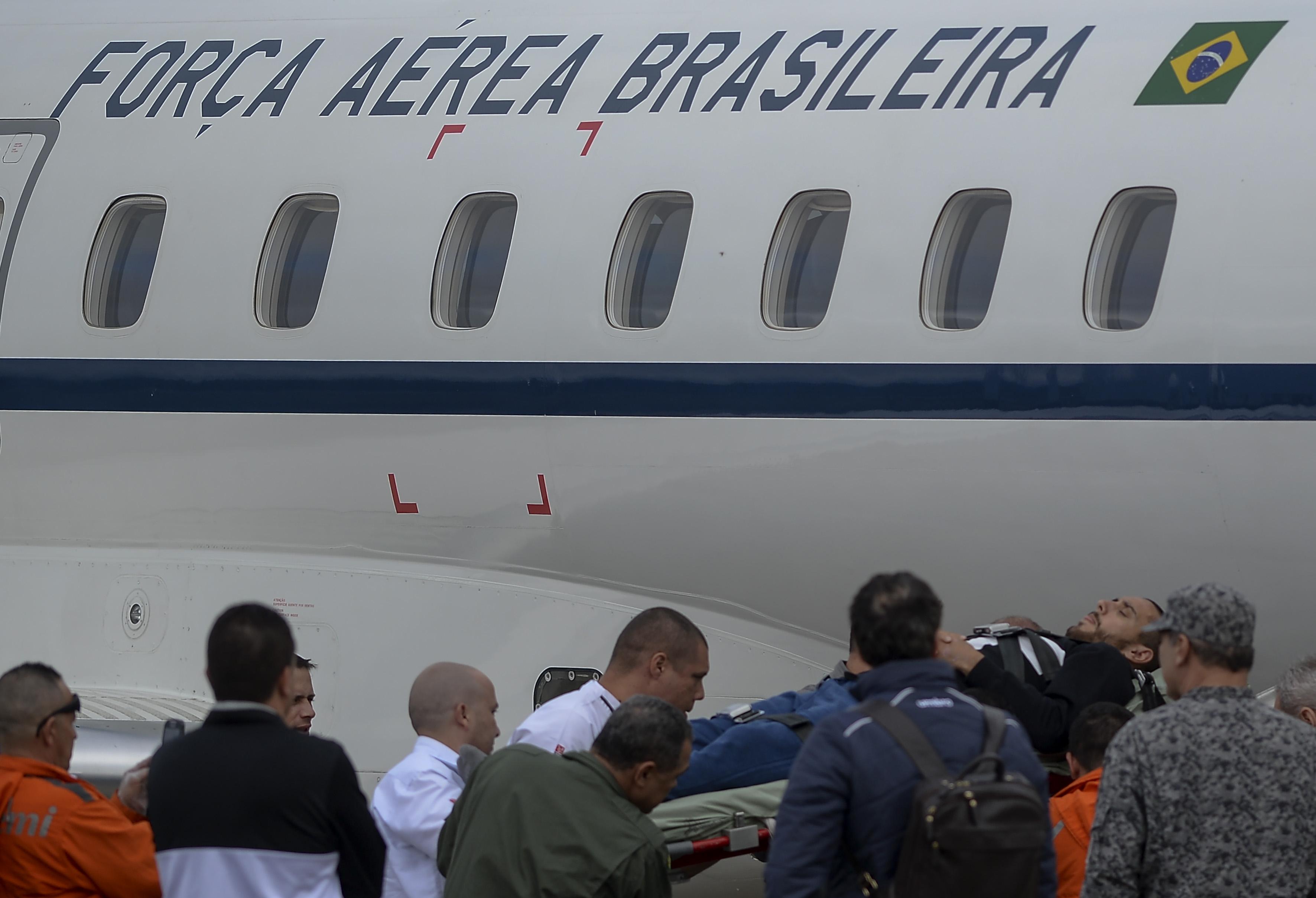 Alan Ruschel (right) being loaded on an plane headed toward Brazil.