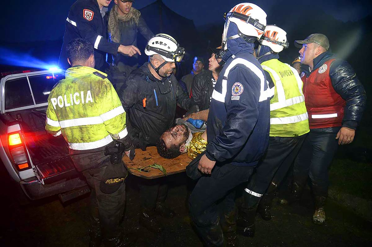 Rescuers carry one of the survivors away from the crash site.