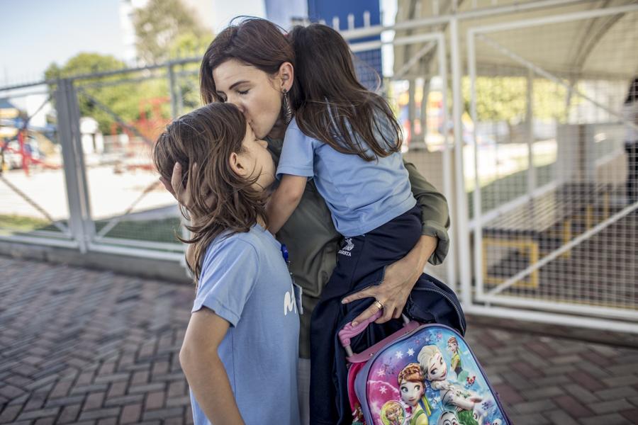 Sirli Freitas (center) embraces her two children Pedro (left) and Mariana.